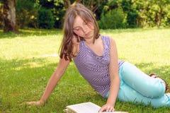 Красивое женское подростковое чтение книга на траве Стоковые Фото