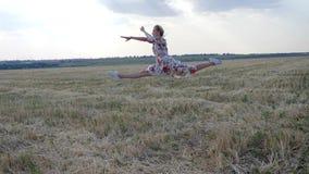 Красивое избежание гимнаста девушки и скакать в замедленное движение делая шпагат в воздухе на поле видеоматериал