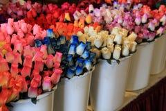Красивое изображение покрашенных деревянных роз в разнообразии цветов, помещенном в белых контейнерах на таблице Стоковая Фотография