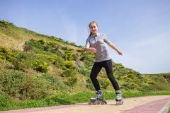 Красивое катание на ролике девочка-подростка в парке Стоковое Фото