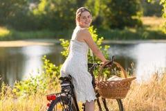 Красивое катание платья молодой женщины вкратце на велосипеде Ла Стоковые Фотографии RF