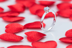 Красивое кольцо с бриллиантом на белой таблице с малым красным цветом чувствовало сердца Стоковое Изображение RF