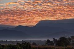 Красивое красное небо с туманом в восходе солнца за горой стоковое фото