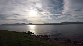 Красивое круглое золотое солнце над высокорослыми горными пиками с спокойным фьордом развевает сток-видео