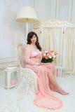 Красивое материнство Беременная в нежном платье персика сидит на стуле Стоковые Фото