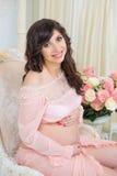 Красивое материнство Беременная в нежном платье персика сидит на стуле Стоковое Изображение