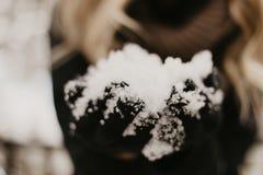 Красивое моделирование молодой женщины связанное в ультрамодных перчатках, пальто, и шарфе усмехаясь и имея потеху со снегом снар стоковые изображения