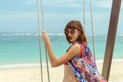Красивое молодое женское усаживание на качании на береге моря человека kuta острова bali городок захода солнца формы красивейшего Стоковые Фотографии RF