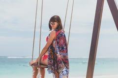 Красивое молодое женское усаживание на качании на береге моря человека kuta острова bali городок захода солнца формы красивейшего Стоковые Фото