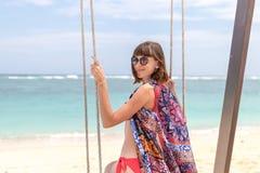 Красивое молодое женское усаживание на качании на береге моря человека kuta острова bali городок захода солнца формы красивейшего Стоковое фото RF