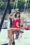 Красивое молодое женское усаживание на качании на береге моря человека kuta острова bali городок захода солнца формы красивейшего Стоковое Изображение