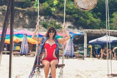 Красивое молодое женское усаживание на качании на береге моря человека kuta острова bali городок захода солнца формы красивейшего Стоковая Фотография RF