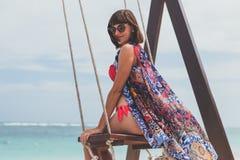 Красивое молодое женское усаживание на качании на береге моря человека kuta острова bali городок захода солнца формы красивейшего Стоковая Фотография