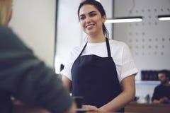 Красивое молодое жизнерадостное женское barista готовое для принимать приказывать Стоковые Изображения