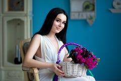 Красивое молодое брюнет в белом платье и ожерелье жемчуга сидят стоковая фотография rf