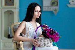 Красивое молодое брюнет в белом платье и ожерелье жемчуга сидят стоковые фотографии rf