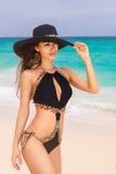 Красивое молодое брюнет в соломенной шляпе и черном купальном костюме Стоковое Изображение RF