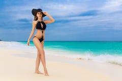 Красивое молодое брюнет в соломенной шляпе и черном купальном костюме стоковое фото rf
