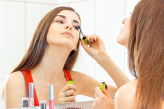 Красивое молодое брюнет стоит прежде чем зеркало и красит глаза Стоковая Фотография
