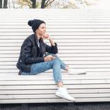 Красивое молодое женское усаживание на скамейке в парке Стоковое Изображение RF
