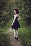 Красивое молодое платье черноты девушки брюнет вкратце идя через древесины Стоковая Фотография RF