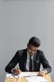 Красивое молодое сочинительство бизнесмена, бизнесмен работая с документами подписывает вверх контракт, сидя на столе на офисе Стоковое Фото
