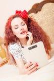 Красивое молодое чтение женщины redhead с таблеткой Стоковые Изображения