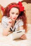 Красивое молодое чтение женщины redhead с таблеткой Стоковое Изображение RF