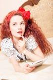 Красивое молодое чтение женщины redhead с таблеткой Стоковые Изображения RF