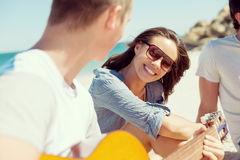 Красивое молодые люди с гитарой на пляже Стоковые Фото