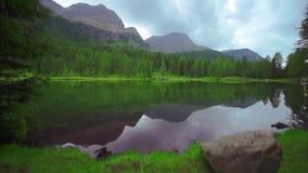 Красивое озеро San Pellegrino которое отражает лес и горы в воде сток-видео
