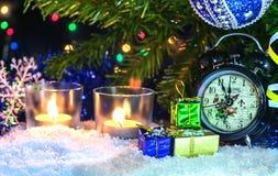 Красивое оформление Нового Года с свечами, часами и гирляндой Стоковое Изображение