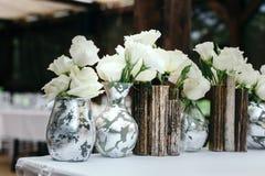Красивое оформление на свадьбе Расположение белых цветков, в вазах reeds На темной предпосылке, конец-вверх Стоковое Изображение