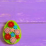 Красивое пасхальное яйцо с деревянными кнопками цветка Пасхальное яйцо войлока изолированное на фиолетовой деревянной предпосылке Стоковое Изображение RF