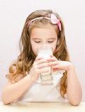 Красивое питьевое молоко маленькой девочки стоковое фото rf