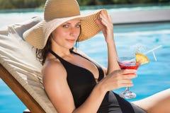 Красивое питье удерживания женщины бассейном Стоковая Фотография