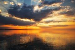 Красивое пламенистое небо захода солнца на пляже Стоковые Фотографии RF