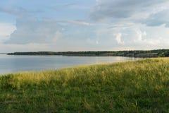 Красивое поле на речном береге под голубым небом Стоковые Изображения RF