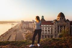 Красивое положение женщины напротив известного фасада и вход к гостинице Gellert на банках Дунай в Будапеште, Венгрии стоковое изображение