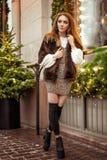 Красивое положение молодой женщины в зиме на улице около оформления р стоковая фотография