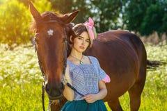 Красивое положение молодой женщины рядом с лошадью в природе стоковое изображение rf