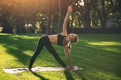 Красивое представление Trikonasana треугольника asana йоги практик молодой женщины в парк на заходе солнца Стоковые Фото