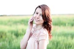 Красивое платье девушки при коричневые волосы, говоря на телефоне, горячий парк летнего дня, ослабляя представления, концепция ст Стоковая Фотография RF