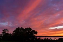 Красивое розовое облачное небо накаляя от солнца вечера установки Стоковое фото RF