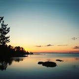 Красивое северное озеро Ladoga ландшафта на заходе солнца Стоковые Изображения