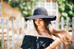 Красивое сексуальное брюнет девушки с коричневым цветом наблюдает в черном платье и черной шляпе с большими brims против фона дер стоковые фото