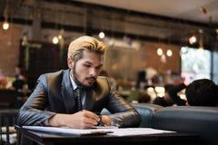 Красивое сочинительство бизнесмена на тетради с чашкой кофе в r Стоковые Фотографии RF