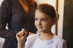 Красивое сочинительство маленькой девочки на классн классном в классе Стоковое Изображение