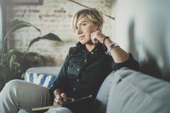Красивое сочинительство молодой женщины что-то в блокноте пока сидящ на кресле на живущей комнате Очаровательный изучать женщины стоковое изображение