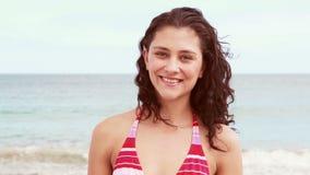 Красивое усмехаясь брюнет в бикини на пляже акции видеоматериалы